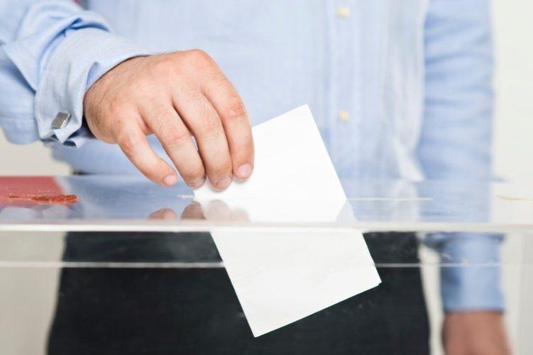 A person putting a ballot into a ballot box