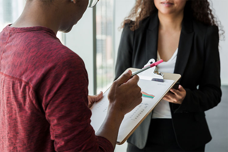 A person holds a clipboard a pen, and is standing in front of a second person, facing eachother.